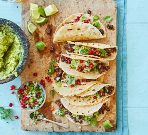 Row of tacos filled with black bean salad, guacamole and salsa