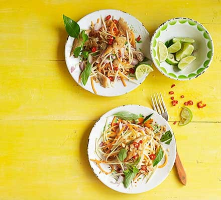 Two plates serving green mango salad with smoked fish