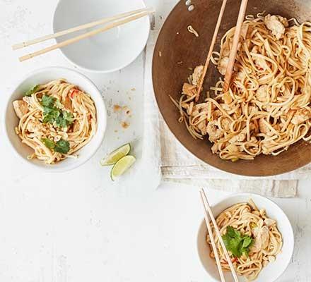 Spicy turkey noodles in a wok alongside two bowls