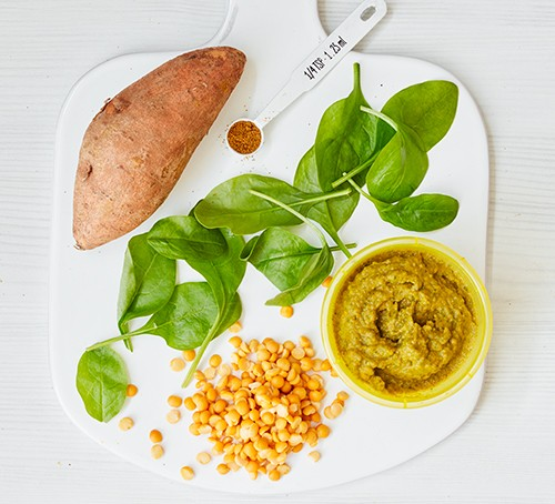 A chopping board with ingredients for spinach, sweet potato & yellow split pea purée