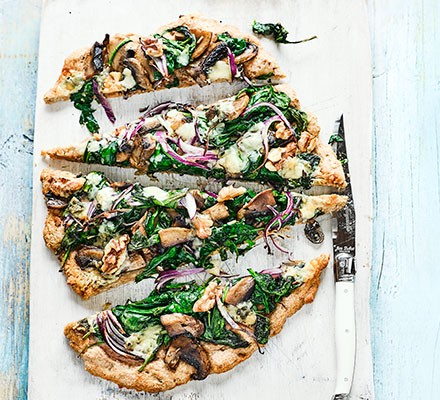 A serving board with spinach & blue cheese pizza on top