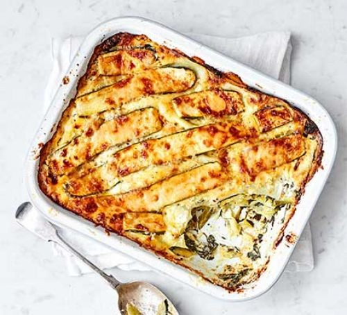 Spinach and courgette lasagne in a rectangular dish with spoon