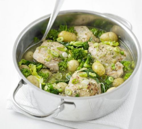 Chicken thighs, vegetables and potatoes in a metal pot with spoon