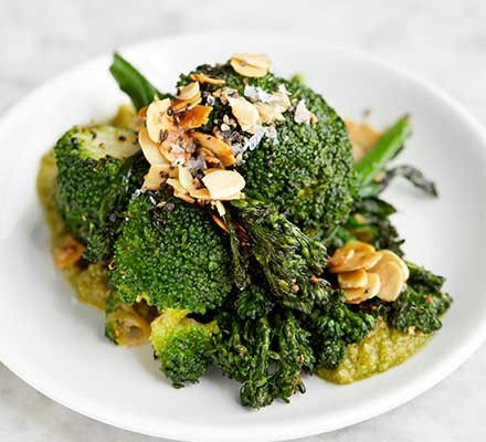 A plate serving sprouting broccoli, green romesco & almonds