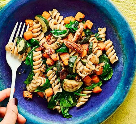 A blue plate serving squash & spinach fusilli with pecans