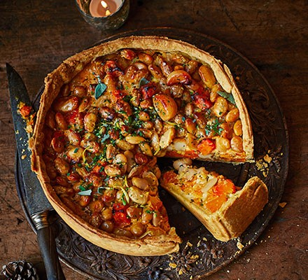 Squash, winter herb & crispy butter bean pie with a slice taken out