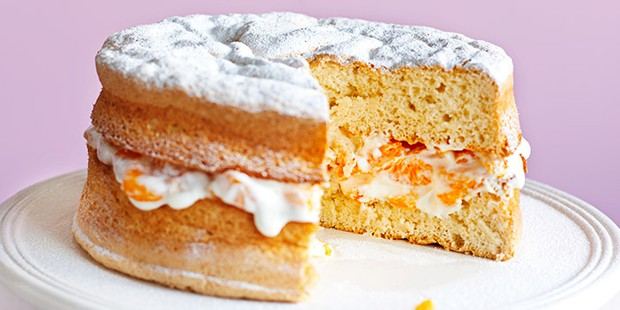 Sponge cake filled with cream and orange fruit topped with icing sugar
