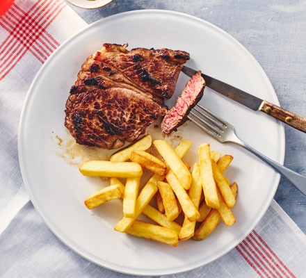 Steak and chips on plate with cutlery