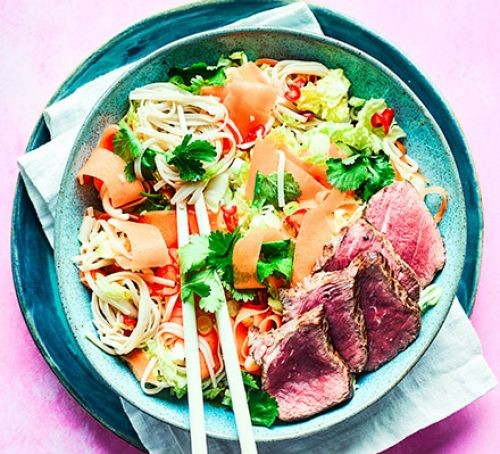A noodle salad topped with steak