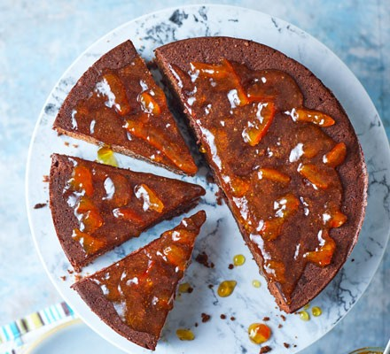 Chocolate cake in slices on platter topped with marmalade