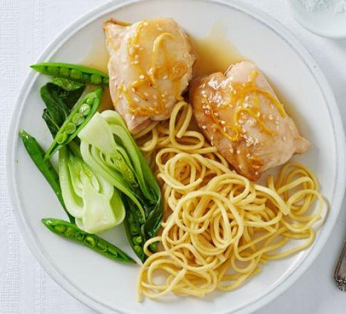 Sticky lemon chicken witb noodles and pak choi on a plate
