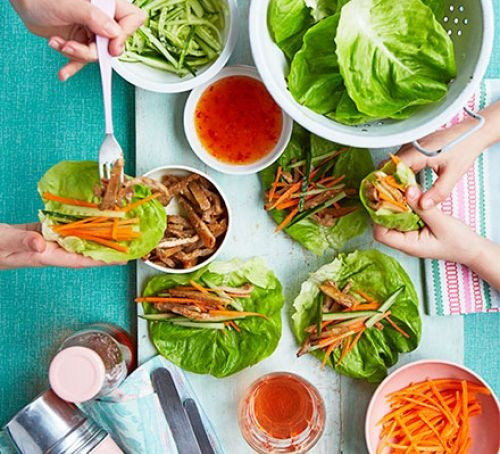 Lettuce and pork wraps being assembled