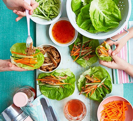 Two people assembling sticky pork lettuce wraps