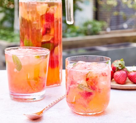 Strawberry cocktails with jug, fruit and stirrer
