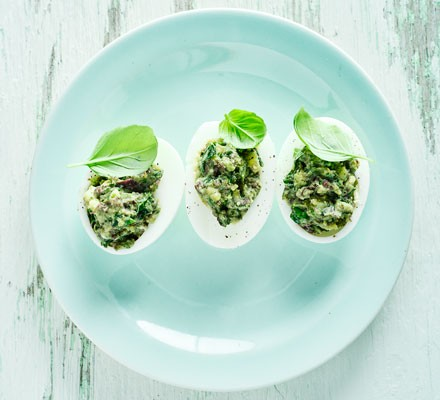 Basil and olive stuffed eggs on a plate with basil leaves
