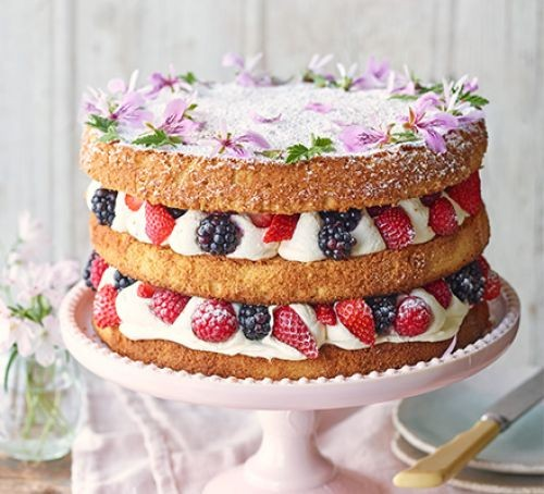 Three-tired sponge cake with berries, icing and flowers