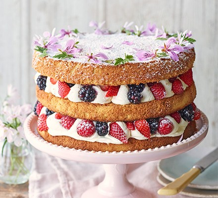 Summer berry cake with rose geranium cream served on a cake stand