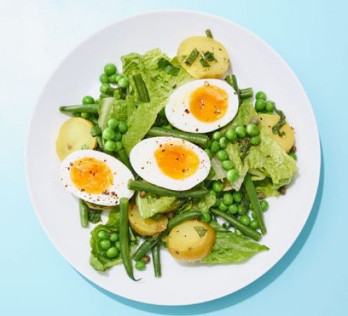 Boiled egg halves with peas, new potatoes and other veg on a plate
