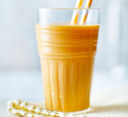 Tropical yellow fruit smoothie in a glass with straws