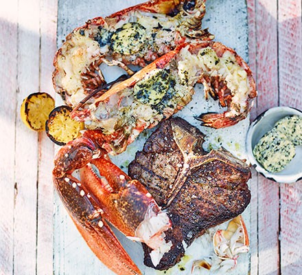 A lobster cut in half, topped with seaweed butter, by a T-bone steak