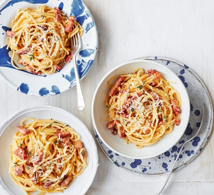 Spaghetti with pancetta and cheese in bowls with cutlery