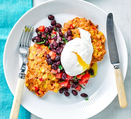 A plate of sweetcorn fritters with black bean salsa and a poached egg