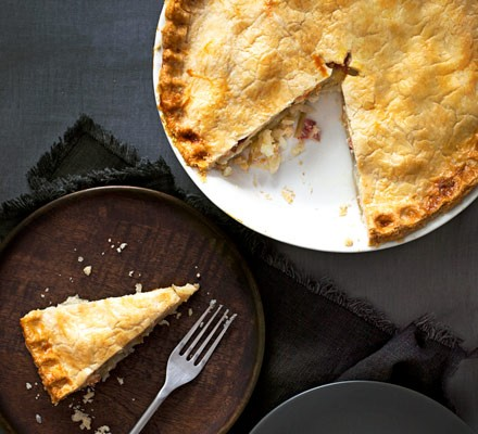 Pie in dish with slice on plate with cutlery