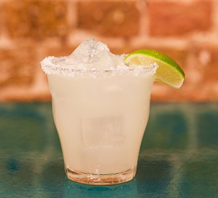 Classic margarita served in a short glass and garnished with a slice of lime