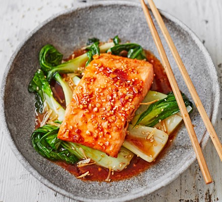 Teriyaki salmon on sesame pak choi with chopsticks