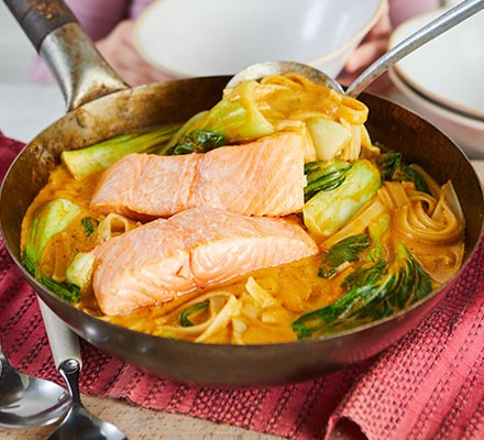 Thai noodle soup with salmon served in a wok