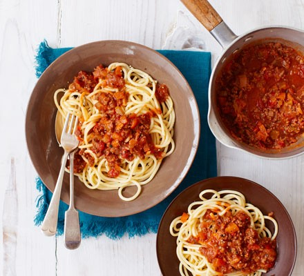 Two bowls of spaghetti topped with bolognese sauce and a pan of extra sauce on the side.
