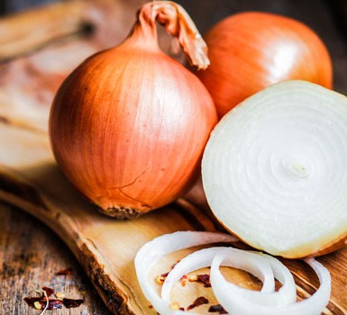 An onion sliced in half and into rings on a chopping board