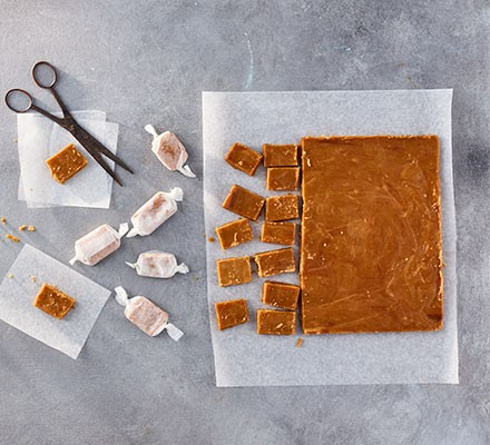 Chewy toffee cut into pieces, some wrapped in paper