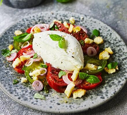 Tomato & mozzarella salad served on a plate with tomato dressing