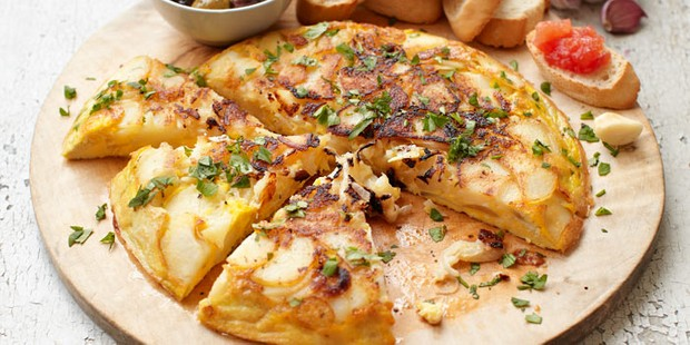 Spanish tortilla on board with tapas