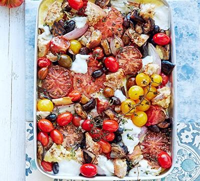 tomato traybake on blue tile with tomatoes