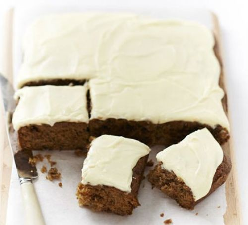Fruit traybake cut into squares, with white icing