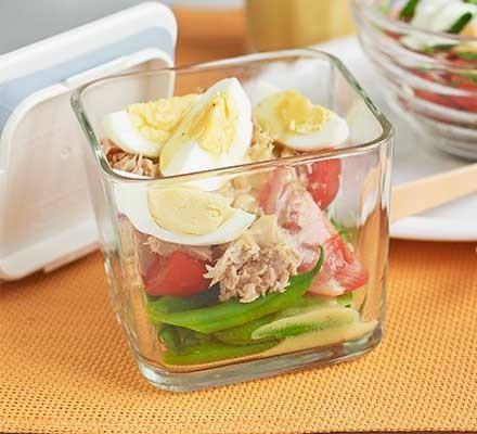 A glass jar filled with tuna Niçoise