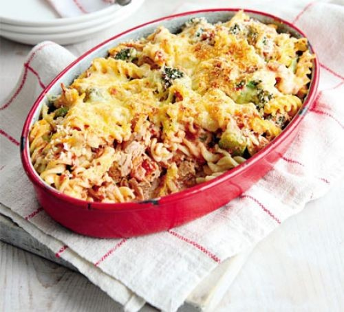 Oval dish of tuna, broccoli pasta bake topped with melting cheese
