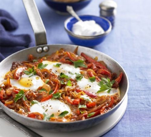 Pan of tomato and pepper sauce with four poached eggs
