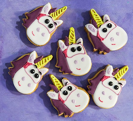 Unicorn iced biscuits on purple background