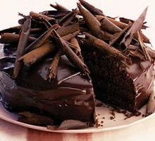 Dark chocolate cake, topped with chocolate curls, against a pale background