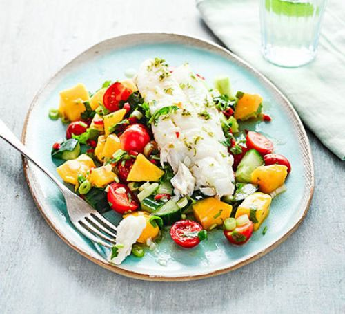 Plate of cucumber, avocado and mango salsa salad topped with cod