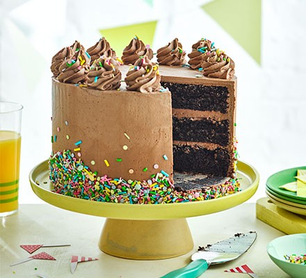 A chocolate birthday cake, with a slice removed, on a cake stand