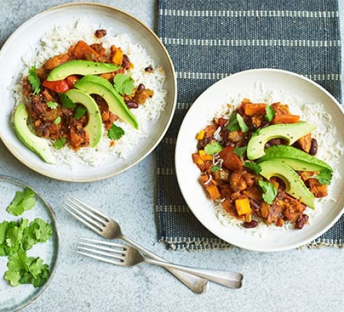 Bowls of vegan chilli topped with sliced avocado