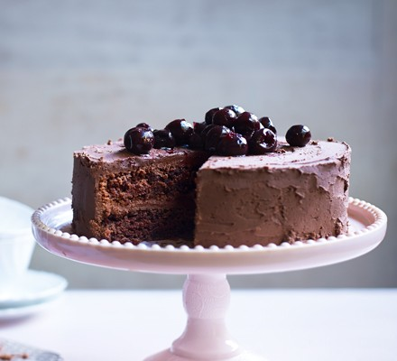 Chocolate cake on cake stand with slice taken, topped with cherries