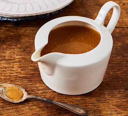 Easiest ever vegan gravy served in a gravy jug, next to a silver spoon