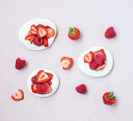 Three vegan meringues garnished with strawberries