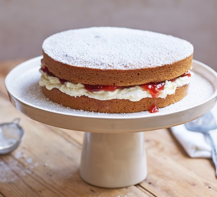 Vegan Victoria sponge cake on a platter dusted with icing sugar