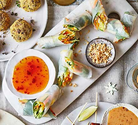 Vegan spring rolls on a serving platter with a chilli dipping sauce